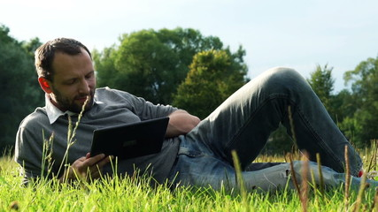 Young man with tablet computer lying on grass in the park
