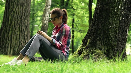 Young woman texting on smartphone in the park