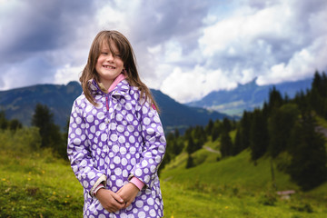 Warm angezogenes kleines Mädchen in den Bergen