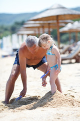 grandfather and granddaughter on the beach