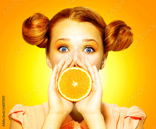 canvas print picture Girl takes juicy orange. Beauty joyful teen girl with freckles