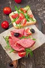 Sandwich with sausage, olive, tomato and arugula