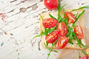 Sandwich with tomato and arugula on the old wooden background