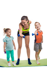 Children with mother doing gymnastic exercises with dumbbells on
