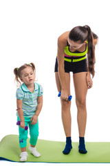 Girl with mother doing gymnastic exercises with dumbbells on a w