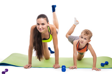 Boy with mother doing gymnastic exercises with dumbbells on a wh