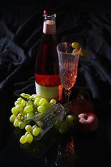 Flasche Fruchtwein mit 2 Gläsern, Weintrauben und Pfirsich