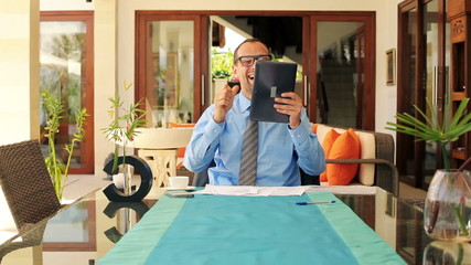Businessman receive great news on tablet computer by table