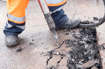 Road worker breaking street asphalt with jackhammer