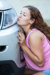 Young Caucasian woman kissing her new car