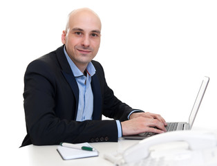 businessman sitting at desk, working on laptop computer