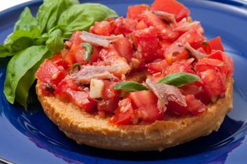 Frisella con pomodori rossi e acciughe su un piatto blu