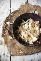 golden onion peels on purple bowl on old burlap