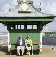 Elderly couple sitting in a seaside shelter Blackpool UK