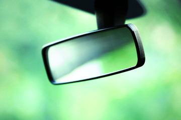 Car rear view mirror on green background