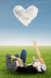 Young couple looking at heart cloud