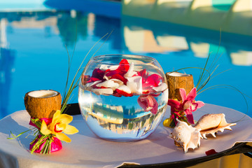two glasses of coconut with orchids, two seashells in a fishbowl
