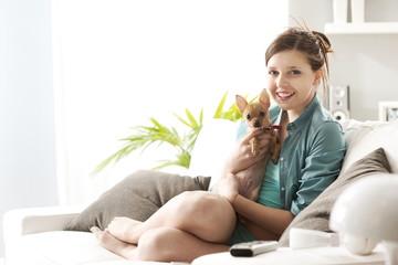Girl playing with dog on sofa