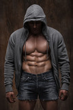 muscular man with open jacket revealing muscular chest and abs