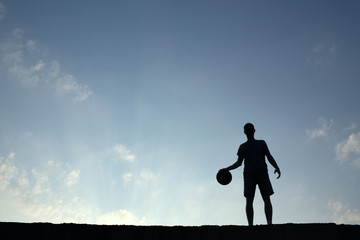 Silhouette of man playin basketball