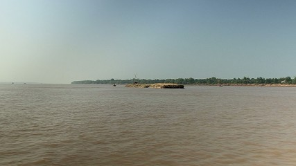 Bamboo rafts on the mekong river towed by a small boat (1)