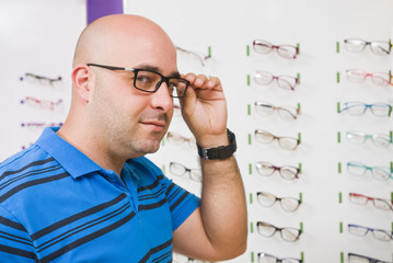 Bald man trying on glasses