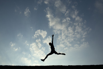 Silhouette of sport man jumping with blue sky and clouds on back
