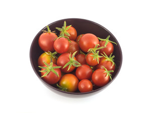 Many ripe tomatoes in purple bowl closeup isolated on white