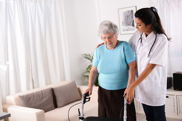 cheerful young rehab nurse helping elderly woman using a walker