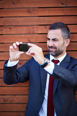 Businessman in a suit taking photograph