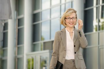 Reifere Geschäftsfrau vor einem Bürogebäude