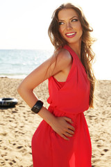 girl with dark hair in elegant dress posing on beach