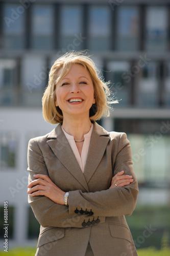 canvas print picture Glückliche Geschäftsfrau vor einem Bürogebäude