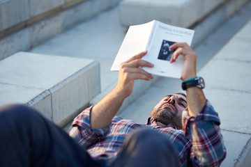 Modern businessman reading outdoors