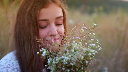 Teen girl with a bouquet of wild flowers in the countryside.