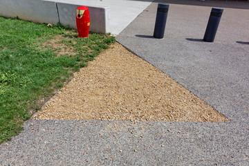 triangle de gravier entre béton et pelouse