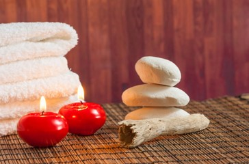 Spa massage with towel stone and red candles warm atmosphere