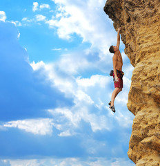 guy hanging on rock