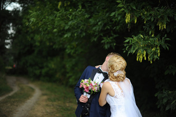 the groom and the bride go on the forest road