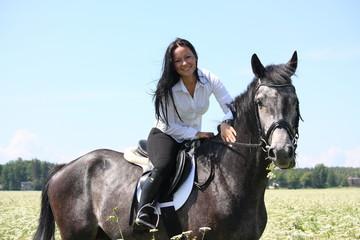 Beautiful young woman riding gray horse