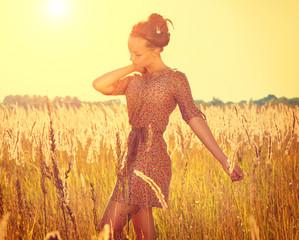 Beautiful teenage girl in short dress posing on the field