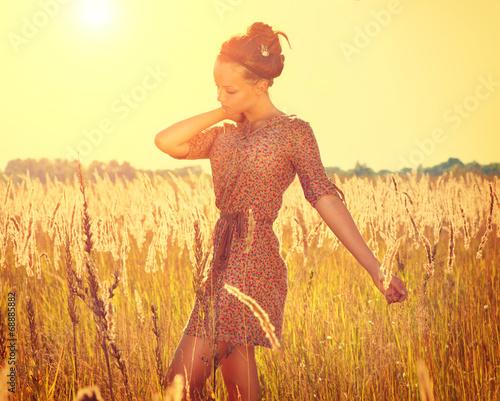 Beautiful teenage girl in short dress posing on the field - 68885882