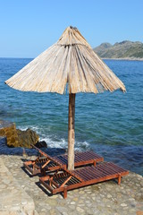 Lounge Chair under the parasol on the beach