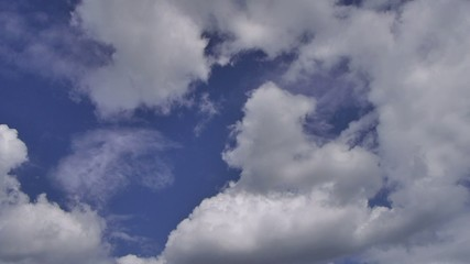 Slow moving clouds in blue sky