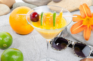 Healthy orange cocktail on a beach environment