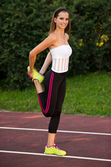 young fit woman stretching in shade outdoor on summer afternoon