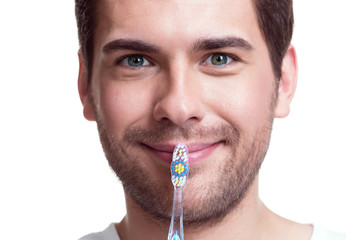Happy young man with a toothbrush.