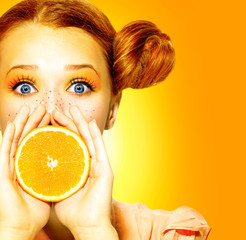 Girl takes juicy orange. Beauty joyful teen girl with freckles