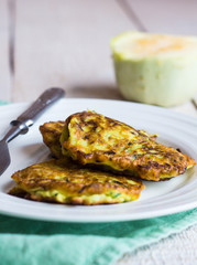 fried zucchini fritters on a white plate, green , white wood