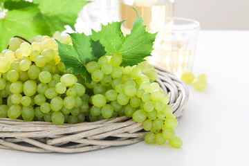 Fresh white grapes in basket and wine